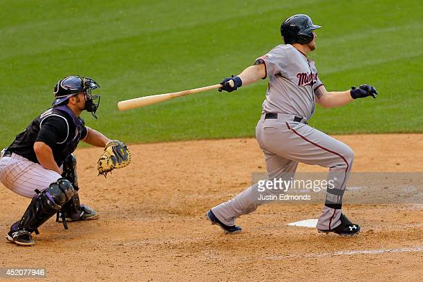 Chris Parmelee of the Minnesota Twins watches his two RBI single during the eighth inning as catcher Michael McKenry of the Colorado Rockies looks on...