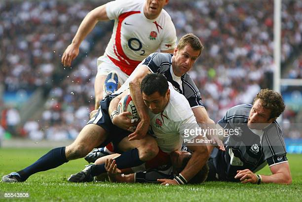 Chris Paterson and Jason White of Scotland attempt to stop Riki Flutey of England as he goes over for England's second try during the RBS 6 Nations...