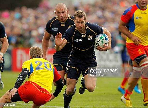 Chris Paterson of Scotland fends off the tackle of Florin Surugiu of Romania during the IRB 2011 Rugby World Cup Pool B match between Scotland and...