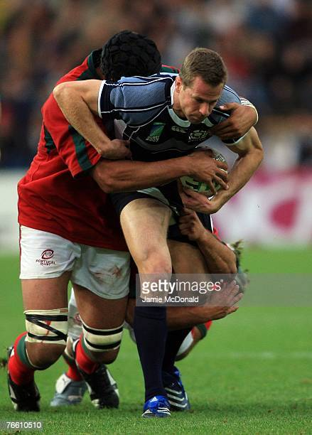 Chris Paterson of Scotland is stopped by Joao Correia and Goncalo Uva of Portugal during match seven of the Rugby World Cup 2007 between Scotland and...