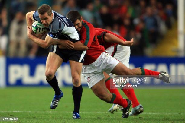 Chris Paterson of Scotland is tackled by Diogo Coutinho of Portugal during match seven of the Rugby World Cup 2007 between Scotland and Portugal at...
