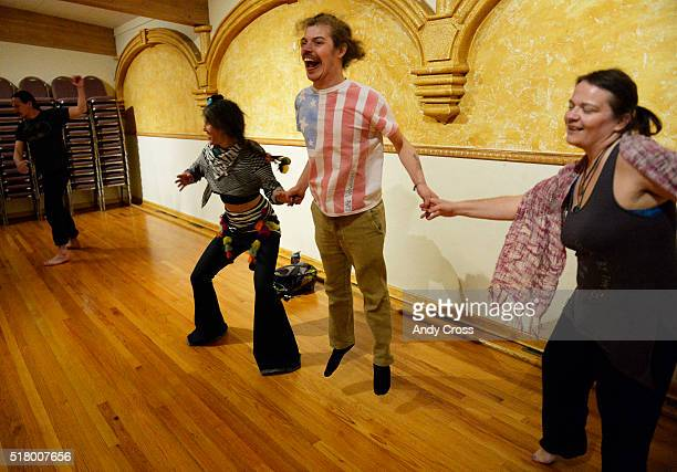 Chris Patton center holds hands and jumps high in the air while dancing with Janel Poffiel left and Sio Straka at the Rhythm Sanctuary at the Sons of...