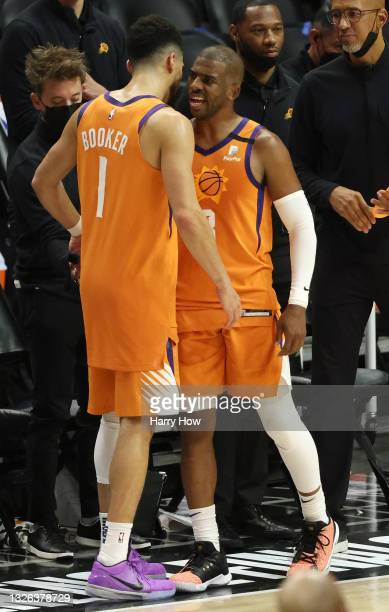 Chris Paul and Devin Booker of the Phoenix Suns hug in the final seconds of the team's win against the LA Clippers during the second half in Game Six...
