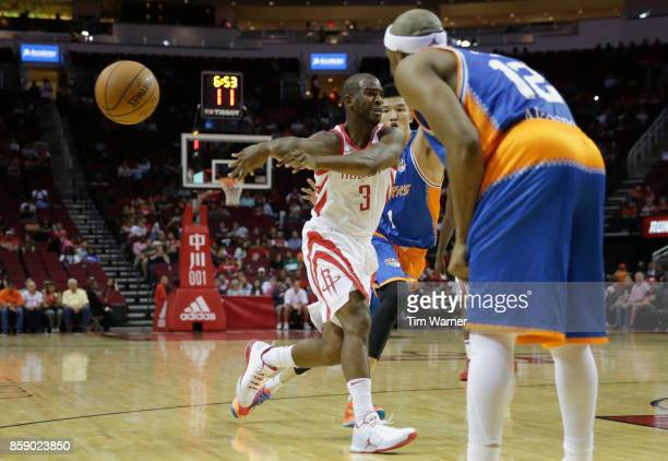 Chris Paul of Houston Rockets passes the ball defended by Car Liang of Shanghai Sharks and Josh Akognon in the first half at Toyota Center on October...