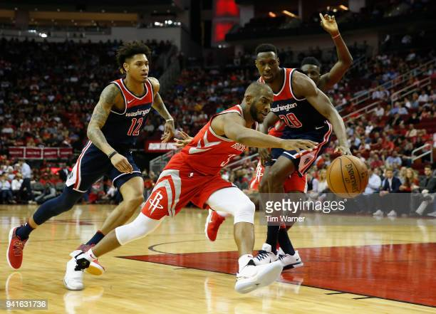 Chris Paul of the Houston Rockets controls a loose ball defended by Ian Mahinmi of the Washington Wizards and Kelly Oubre Jr #12 in the first half at...
