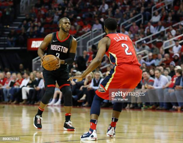 Chris Paul of the Houston Rockets controls the ball defended by Ian Clark of the New Orleans Pelicans in the first half at Toyota Center on December...