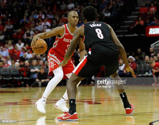 Chris Paul of the Houston Rockets controls the ball defended by AlFarouq Aminu of the Portland Trail Blazers in the second half at Toyota Center on...