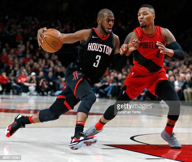 Chris Paul of the Houston Rockets drives against Damian Lillard of the Portland Trail Blazers at Moda Center on December 9 2017 in Portland Oregon...