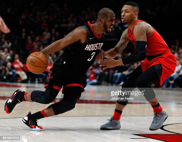Chris Paul of the Houston Rockets drives against Damian Lillard of the Portland Trail Blazers at Moda Center on December 9 2017 in Portland Oregon...