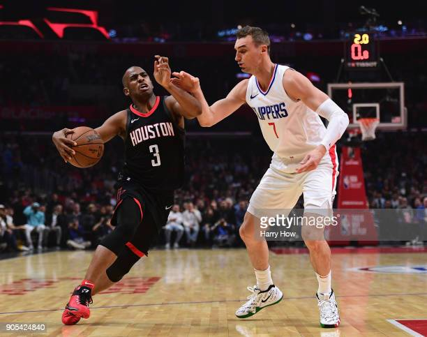 Chris Paul of the Houston Rockets drives on Sam Dekker of the LA Clippers during the first half at Staples Center on January 15 2018 in Los Angeles...