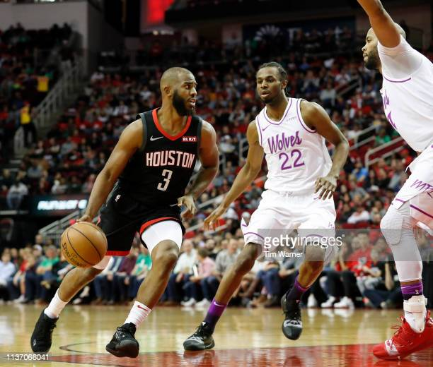 Chris Paul of the Houston Rockets drives to the basket defended by Andrew Wiggins of the Minnesota Timberwolves and Taj Gibson in the first half at...