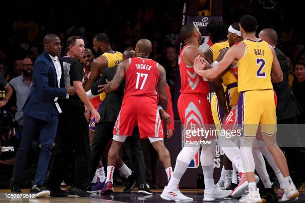 Chris Paul of the Houston Rockets is restrained by LeBron James of the Los Angeles Lakers after a fight involving Rajon Rondo and Brandon Ingram of...