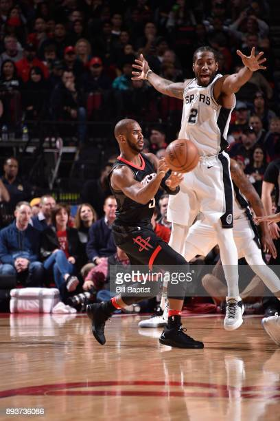 Chris Paul of the Houston Rockets passes the ball against Kawhi Leonard of the San Antonio Spurs on December 15 2017 at the Toyota Center in Houston...