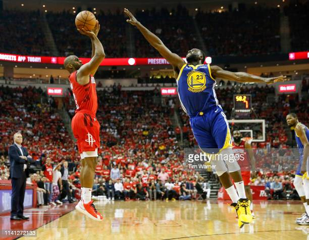 Chris Paul of the Houston Rockets takes a three point shot defended by Draymond Green of the Golden State Warriors in the first half during Game...
