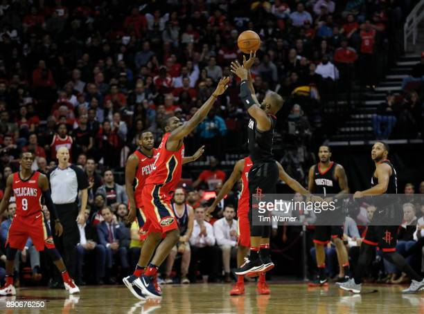 Chris Paul of the Houston Rockets takes a three point shot defended by Jalen Jones of the New Orleans Pelicans in the second half at Toyota Center on...