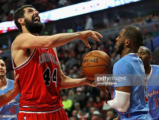 Chris Paul of the Los Angeles Clippers knocks the ball away from Nikola Mirotic of the Chicago Bulls at the United Center on March 1 2015 in Chicago...