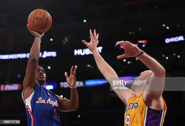 Chris Paul of the Los Angeles Clippers shoots over Chris Kaman of the Los Angeles Lakers at Staples Center on October 29 2013 in Los Angeles...