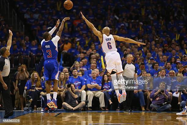 Chris Paul of the Los Angeles Clippers takes a shot against Derek Fisher of the Oklahoma City Thunder in Game One of the Western Conference...