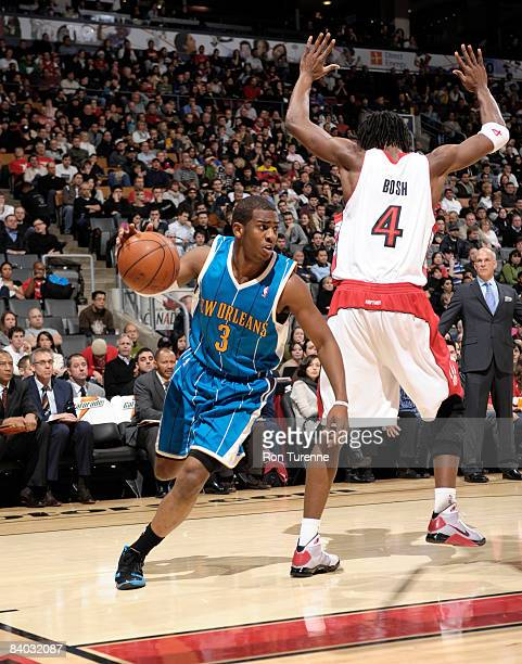 Chris Paul of the New Orleans Hornets drives past Chris Bosh of the Toronto Raptors on December 14 2008 at the Air Canada Centre in Toronto Ontario...