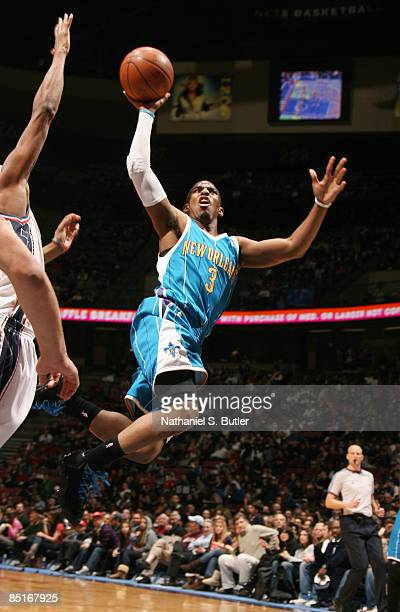 Chris Paul of the New Orleans Hornets shoots over Trenton Hassell of the New Jersey Nets on March 1 2009 at the IZOD Center in East Rutherford New...