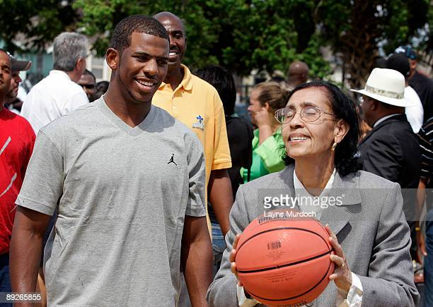 Chris Paul of the New Orleans Hornets watches Mary June Willard shoot a basket before dedicating the Hardin Playground basketball court painted to...