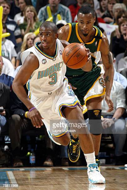 Chris Paul of the New Orleans/Oklahoma City Hornets dribbles the ball while being guarded by Rashard Lewis of the Seattle SuperSonics on April 4 2007...