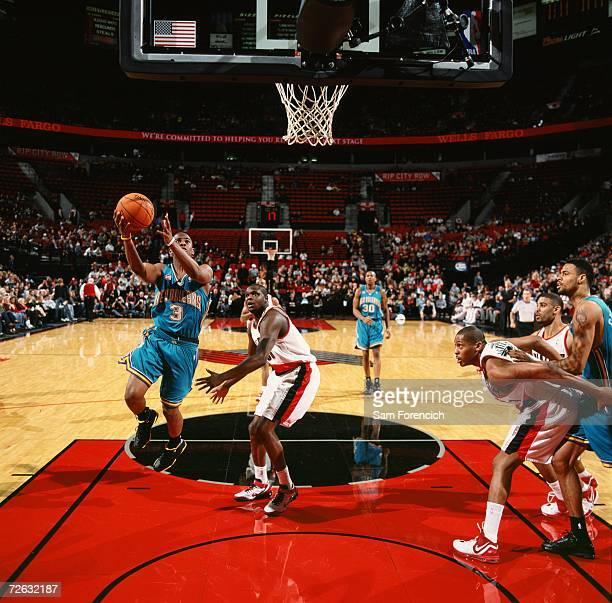 Chris Paul of the New Orleans/Oklahoma City Hornets drives to the basket for a layup past Zach Randolph of the Portland Trail Blazers during a game...