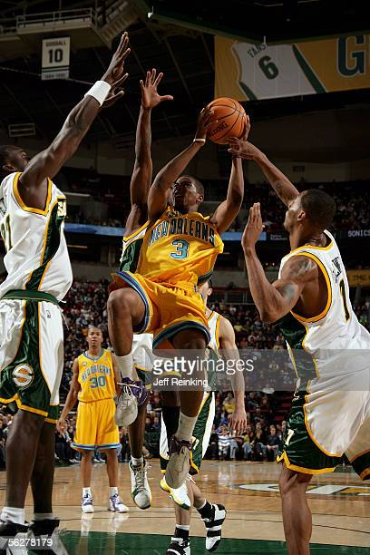 Chris Paul of the New Orleans/Oklahoma City Hornets drives to the basket against Johan Petro and Rashard Lewis of the Seattle SuperSonics on November...