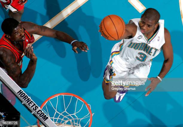 Chris Paul of the New Orleans/Oklahoma City Hornets gets in for a layup past Marvin Williams of the Atlanta Hawks during a NBA game on November 18,...