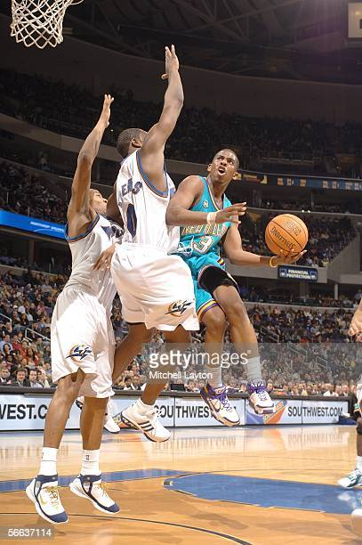 Chris Paul of the New Orleans/Oklahoma City Hornets goes to the basket against Caron Butler and Gilbert Arenas of the Washington Wizards in a NBA...