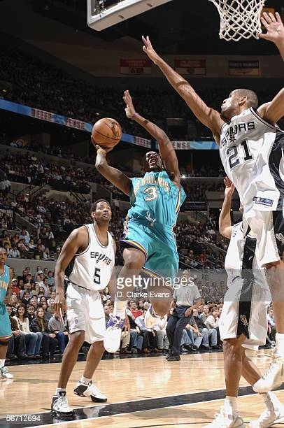 Chris Paul of the New Orleans/Oklahoma City Hornets goes to the basket against Robert Horry and Tim Duncan of the San Antonio Spurs on December 29...