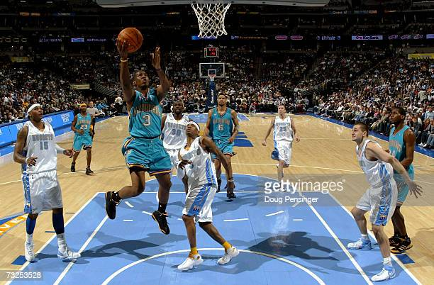 Chris Paul of the New Orleans/Oklahoma City Hornets lays up a shot between Carmelo Anthony and Allen Iverson of the Denver Nuggets as the Hornets...