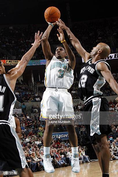 Chris Paul of the New Orleans/Oklahoma City Hornets shoots a jump shot against Tim Duncan and Bruce Bowen of the San Antonio Spurs during an NBA game...