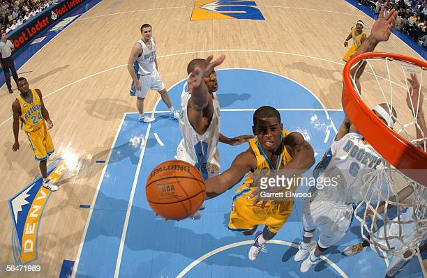 Chris Paul of the New Orleans/Oklahoma City Hornets takes the ball to the basket during a game against the Denver Nuggets at the Pepsi Center on...