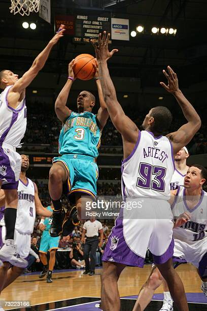 Chris Paul of the New Orleans/Oklahoma City Hornets takes the ball to the basket against Kevin Martin and Ron Artest of the Sacramento Kings on...