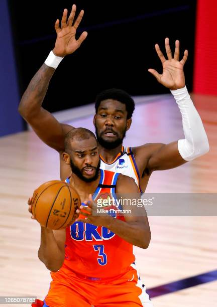 Chris Paul of the Oklahoma City Thunder is pressured by Deandre Ayton of the Phoenix Suns during the third quarter at The Field House at ESPN Wide...