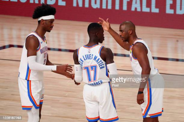 Chris Paul of the Oklahoma City Thunder talks with guard Shai Gilgeous-Alexander and Dennis Schroder during the first half of game four against the...