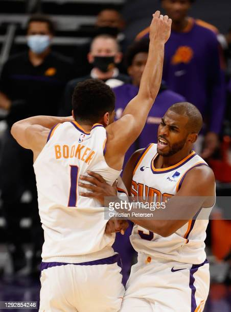 Chris Paul of the Phoenix Suns celebrates with Devin Booker after scoring against the Dallas Mavericks during the final moments of the second half of...