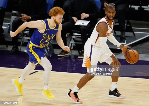 Chris Paul of the Phoenix Suns handles the ball ahead of Nico Mannion of the Golden State Warriors during the second half of the NBA game at Phoenix...