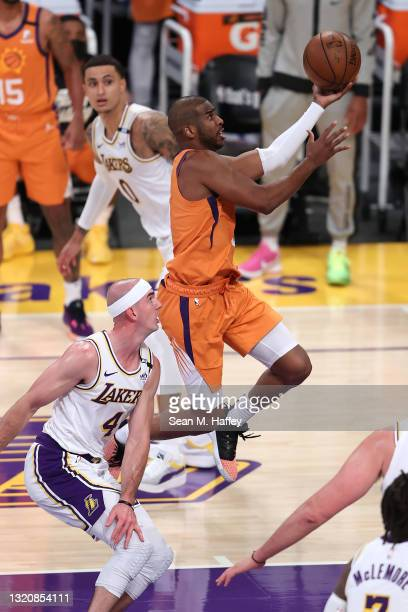 Chris Paul of the Phoenix Suns lays up past the defense of Alex Caruso of the Los Angeles Lakers during the second half of Game Four of the Western...