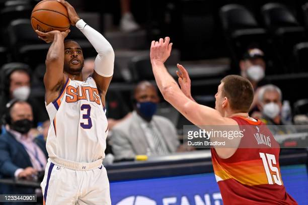 Chris Paul of the Phoenix Suns shoots and scores on a three-point attempt under coverage by Nikola Jokic of the Denver Nuggets in Game Four of the...