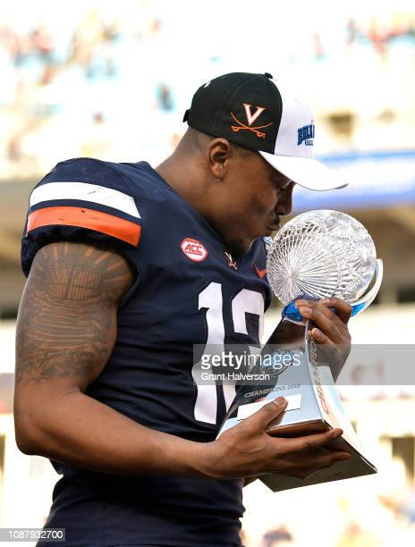 Chris Peace of the Virginia Cavaliers kisses the trophy after a win against the South Carolina Gamecocks during the Belk Bowl at Bank of America...