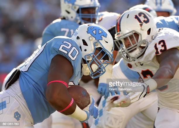 Chris Peace of the Virginia Cavaliers tackles Johnathon Sutton of the North Carolina Tar Heels during their game at Kenan Stadium on October 14 2017...