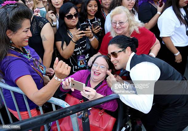 Chris Perez takes photos with fans during Madame Tussauds Hollywood's unveiling of GRAMMY award winner and cultural icon Selena Quintanilla...