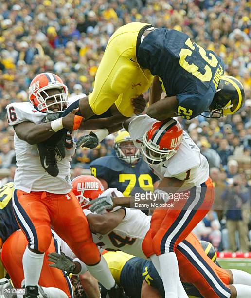 Chris Perry of the Michigan Wolverines jumps over and past Antonio Mason and Marc Jackson of the Illinois Fighting Illini to score his second...
