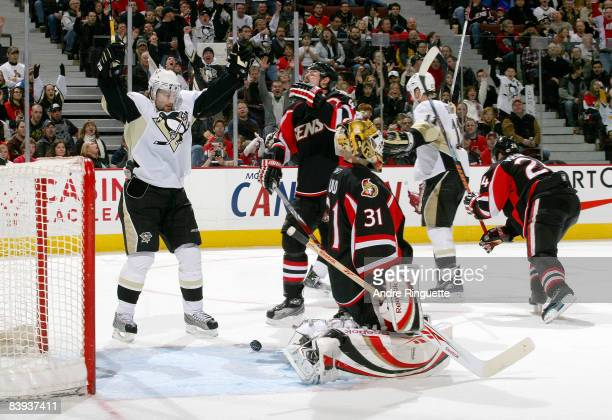 Chris Phillips and Alex Auld of the Ottawa Senators react as Petr Sykora of the Pittsburgh Penguins celebrates a second period goal at Scotiabank...