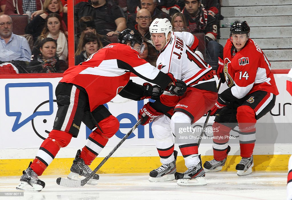 Chris Phillips #4 of the Ottawa Senators checks Jordan Staal #11 of the Carolina Hurricanes during an NHL game at Scotiabank Place on February 7, 2013 in Ottawa, Ontario, Canada.