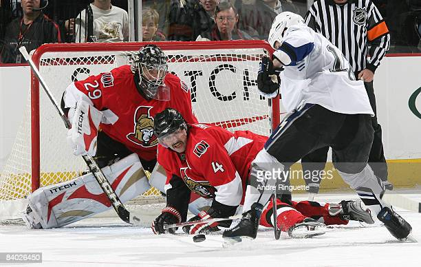 Chris Phillips of the Ottawa Senators chips a rebound away from Adam Hall of the Tampa Bay Lightning outside the crease of Martin Gerber of the...