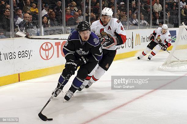 Chris Phillips of the Ottawa Senators defends from behind against Drew Doughty of the Los Angeles Kings during the game on December 3, 2009 at...