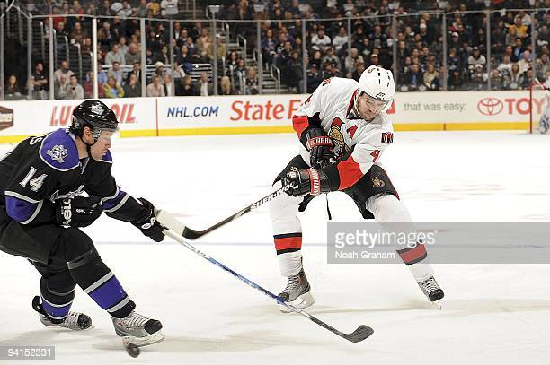 Chris Phillips of the Ottawa Senators passes the puck as Justin Williams of the Los Angeles Kings defends during the game on December 3, 2009 at...
